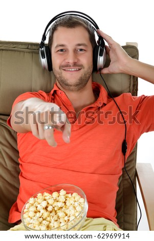 Young handsome caucasian man with popcorn on sofa listening music at headphones and pointing . Studio shot. White background. - stock photo