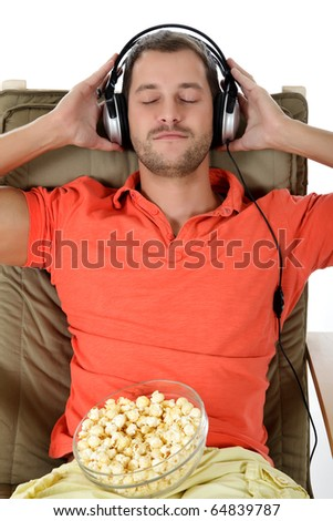 Young handsome caucasian man with popcorn on sofa listening music at headphones. Studio shot. White background. - stock photo