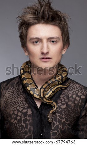 Young, handsome caucasian man with snake around his neck; grey background, a lot of copyspace available - stock photo