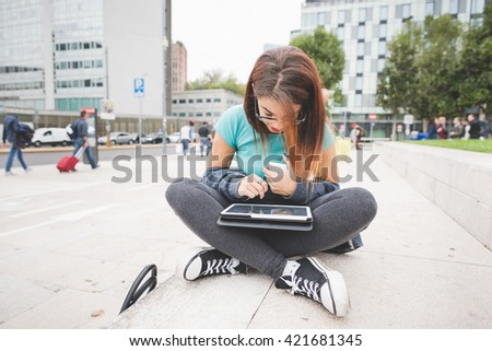 young handsome caucasian reddish hair woman sitting on a small wall leg crossed, tablet on her knee, holding smart phone, looking downward the screen - technology, communication, multitasking concept - stock photo