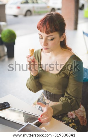 Young handsome caucasian redhead woman sitting in a bar using tablet while eating ice cream, looking downward - technology, social network, multitasking concept - wearing green shirt and floral skirt