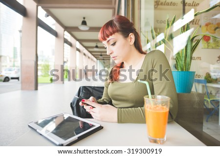 Young handsome caucasian redhead woman using smartphone sitting in bar, with a juice and a tablet on the table, looking downward, tapping the screen - technology, social network, multitasking concept - stock photo