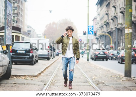 Young handsome cauciasain curly hair man walking in the street of the city, talking smartphone, overlooking pensive - communicaiton, technology, thoughtful concept