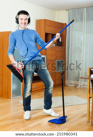 Young handsome cheerful man cleaning and playing with broom and dustpan in living room at home - stock photo