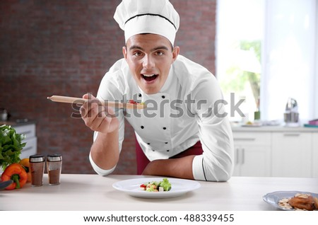 Young handsome chef cook tasting salad