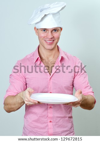 Young handsome chef holding empty plate - stock photo