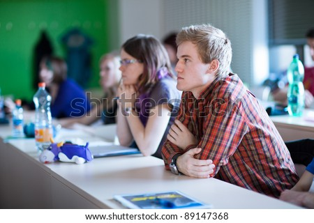 young, handsome college student sitting in a classroom full of students during class - stock photo