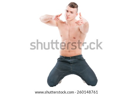 Young, handsome, confident and muscular male model on his knees poiting to the camera - stock photo