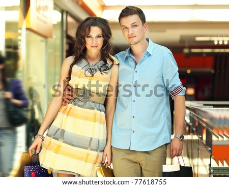 Young handsome couple in a shopping passage - stock photo