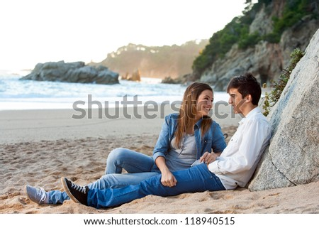 Young handsome couple sitting on beach at sunset.