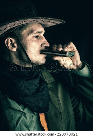 Young handsome cowboy in brown hat drinking alcohol from a flask on a black background - stock photo