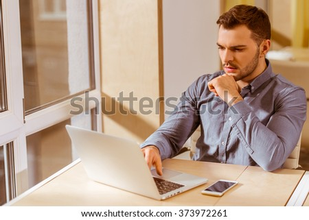 Young handsome dark-haired businessman in casual clothes using laptop and thinking while working in office - stock photo