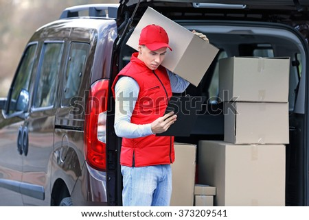 Young handsome delivery man standing near the car with boxes and packages, outdoors - stock photo