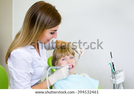 Young handsome dentist treats tooth child, a woman dentist.Dentist