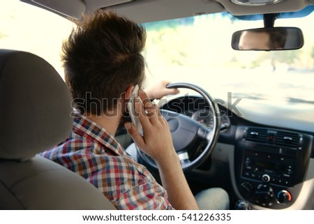 Young handsome driver using mobile phone while driving car