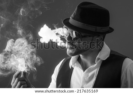 Young handsome elegant stylish male model wearing sunglasses and hat smoking a cigarette black and white portrait - stock photo
