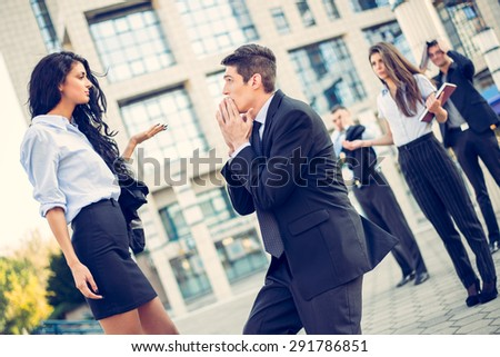Young handsome, elegantly dressed businessman on the street in front of office building, kneeling with folded hands in front of a young attractive business woman while they watching colleagues.