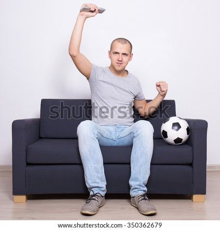 young handsome excited soccer fan watching game on television - stock photo