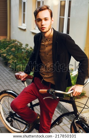 Young handsome fashion dressed man posing outdoor with vintage classic cruiser bicycle on the street autumn portrait  - stock photo