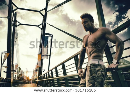 Young handsome fashion model man outdoors. Trendy handsome guy with trendy hairstyle outdoors. Photo has an INTERNATIONAL FILM GRAIN.