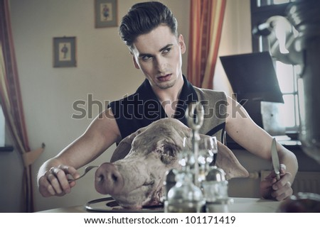 Young handsome fashioned men eat pig - stock photo