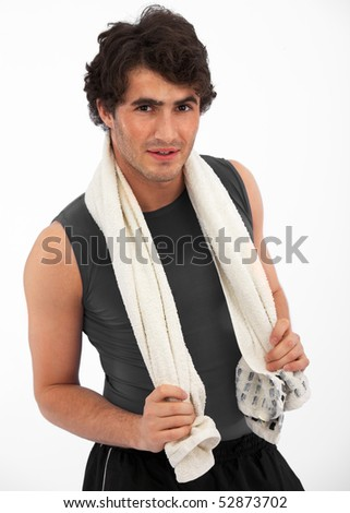 Young, handsome fitness model posing with towel after a workout against white background - stock photo