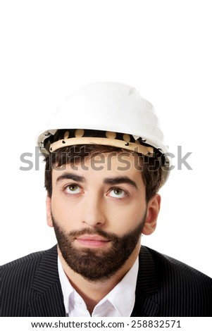 Young handsome foreman with hard hat looking up.  - stock photo