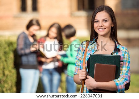 Young handsome girl, student at the college.  Her classmates in the background. - stock photo