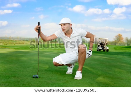 young handsome golfer on  a golf course - stock photo