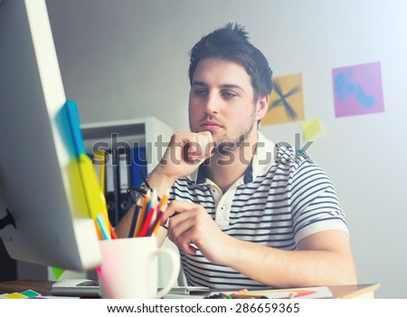 Young Handsome Graphic designer using graphic tablet to do his work at desk - stock photo