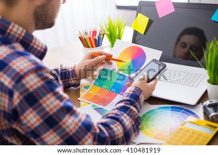 Young Handsome Graphic designer using graphics tablet to do his work at desk