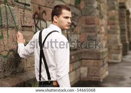 young handsome guy against the stone wall - stock photo