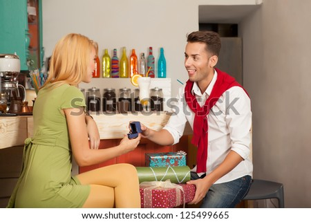 young handsome guy asking his girlfriends hand in marriage in colorful cafe with gift boxes - stock photo
