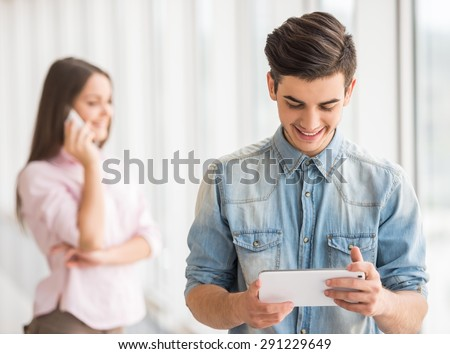 Young handsome guy dressed casual using digital tablet while his girlfriend talking on phone. - stock photo