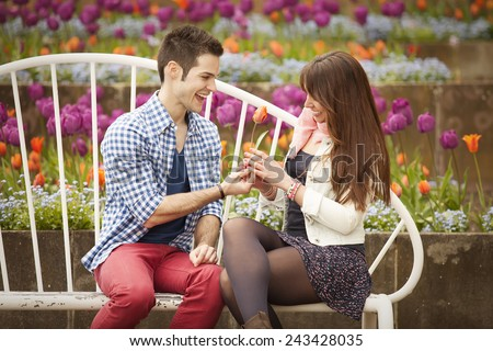 young handsome guy giving tulip to attractive girl in spring London park - stock photo