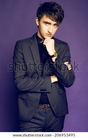 Young handsome guy posing at studio in stylish grey suit, businessman style, violet purple studio background.   - stock photo