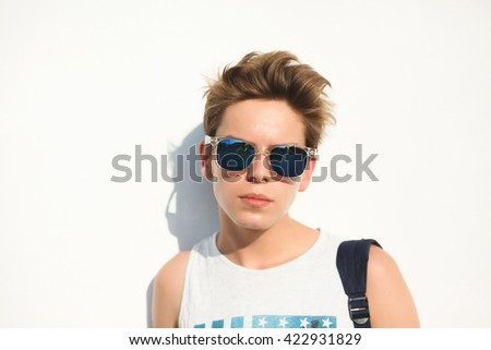 young handsome guy teen, wearing sunglasses with a fashionable hairstyle posing in front of a white wall, isolated, outdoor, portrait, backpack  - stock photo