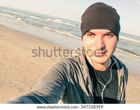 Young handsome guy with male sport clothes taking selfie at beach in autumn season -  Healthy lifestyle and fitness training concept - Vintage desaturated filter look with tilted horizon composition - stock photo