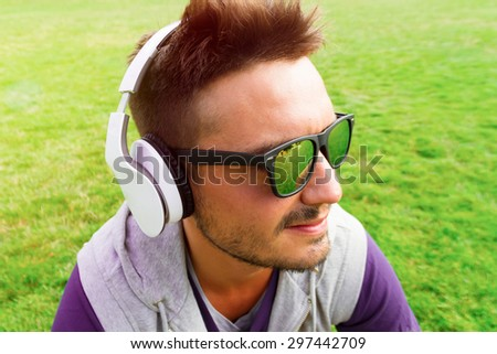 Young handsome hipster beard man relaxed at sunny day on the park, after crossfitl training, wearing wireless headphones,sunglasses, listening music, enjoy his holiday. Trendy guy,stylish male haircut - stock photo