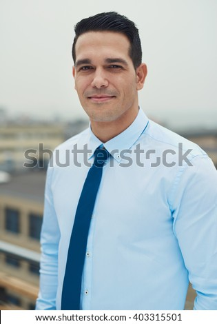 Young handsome Hispanic business man standing on a rooftop of an urban commercial building smiling at the camera - stock photo