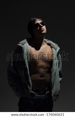 Young handsome macho man in sunglasses revealing muscular chest and torso