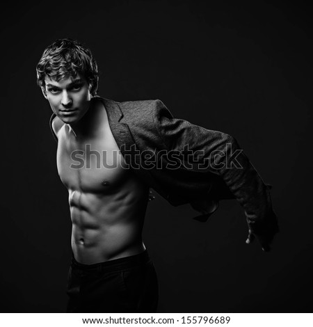 Young handsome macho man with muscle abdominal and open jacket. Black and white studio shoot