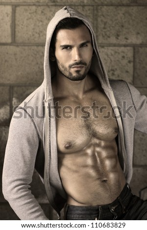 Young handsome macho man with open jacket revealing muscular chest and abs - stock photo