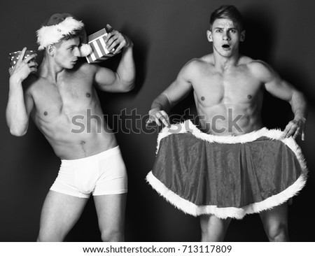 young handsome macho santa twins with sexy muscular athletic strong body has bare torso and strong belly in christmas cape or xmas hat with colorful present boxes or gifts on green studio background
