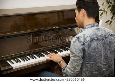 Young handsome male artist playing his wooden classical upright piano, indoor portrait - stock photo