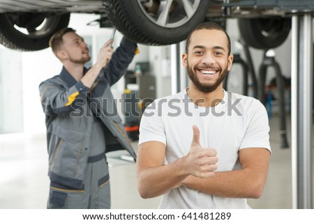 Young handsome male car owner smiling happily showing thumbs up posing in front of professional mechanic repairing his car copyspace owner ownership maintenance help assistance service client customer