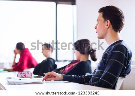 young, handsome male college student sitting in a classroom full of students during class (color toned image; shallow DOF) - stock photo