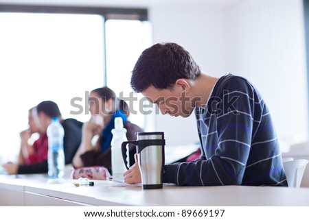 young, handsome male college student sitting in a classroom full of students during class (color toned image; shallow DOF)