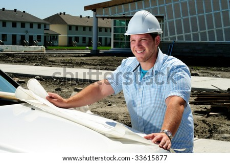 Young Handsome Male Construction Site Foreman, Checking The Blueprints - stock photo