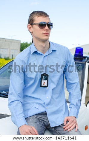 Young handsome male FBI agent near the car - stock photo